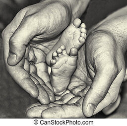 Newborn baby foot in fathers hands, black and white