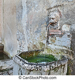 ancient drinking fountain - water running in a public...