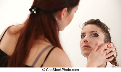 Stage make-up - Make-up artist preparing fashion model for...