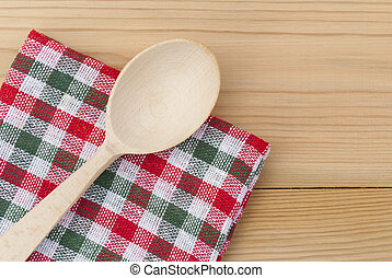 Wooden spoon and a checkered napkin on the table.