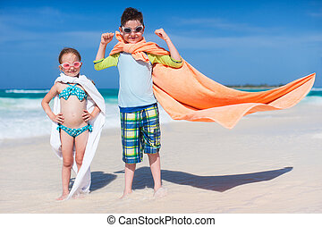 Superheros at a beach - Little kids playing superheroes at a...