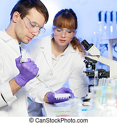 Health care professionals in lab. - Young male researcher...