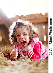 Joyful Girl in Hay Laughing - Joyful little girl having fun...
