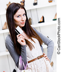 Female holds credit card in footwear shop - Lady hands...