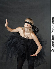 female beauty-portrait with tutu in front of a dark...