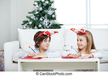 Siblings Writing Letter To Santa Claus During Christmas -...