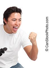 Yeah I beat you! - Young man having fun playing video games,...