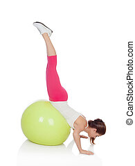 Attractive woman doing pilates with a big green ball...