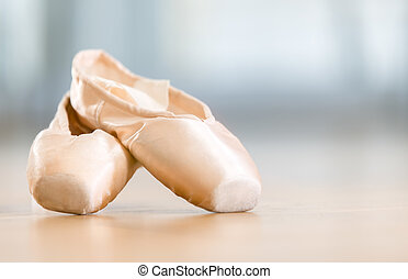 Close-up view of pointes for ballet lying on the wooden...