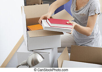 Woman packing herself - Woman is packing her books and stuff...