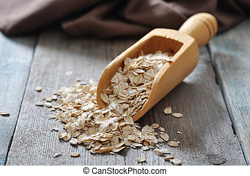 oat flakes in wooden  scoop on wooden background