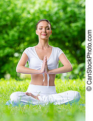 Woman with eyes closed in asana position prayer gesturing