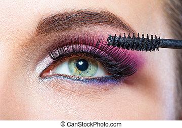 Close up shot of female eye and brush applying mascara -...