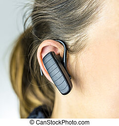 Female operator with bluetooth phone - Detail of female...