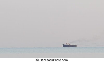 Tugboat tugging a large barge in an overcast day - Long shot...