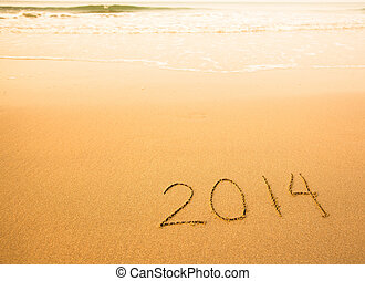 2014 - written in sand on beach texture, soft wave of the sea.