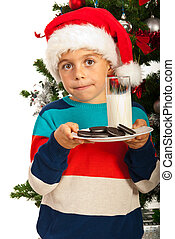 Christmas boy holding milk and biscuits and standing in...