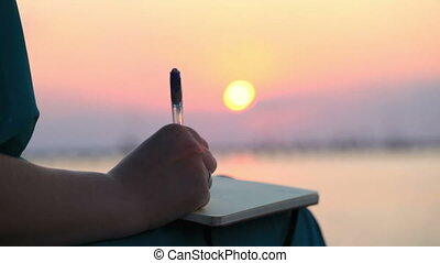 Woman writing in her diary at sunset - Close up view of the...