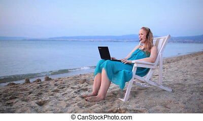 Woman talking skype at the beach - Woman relaxing at the...