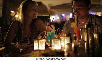 Romantic young couple enjoying drinks in a date in an...