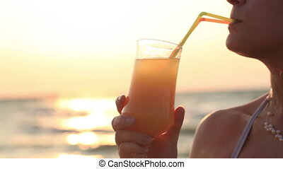 Woman sipping a refreshing cocktail at sunset - Woman...