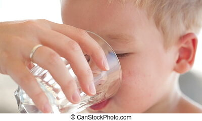 Little boy drinkng a glass of fresh water