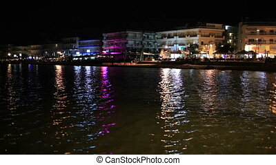 Illuminated waterfront buildings at night casting colourful...
