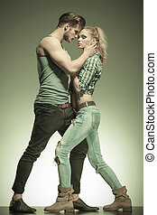 young passionate fashion couple standing embraced