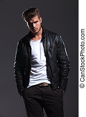 man in leather jacket posing with his hands in pockets -...