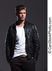 young man in leather jacket is looking away while standing...
