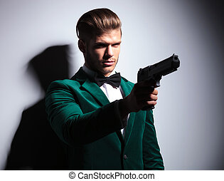 James Bond wannabe young assasin pointing his big pistol to...