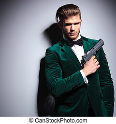 James Bond wannabe young assasin with a big pistol in his...