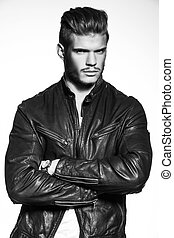 fashion model in leather jacket standing with hands crossed...