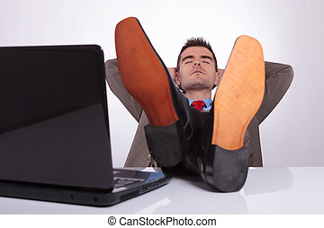 young business man sleeps at work with feet on desk - young...