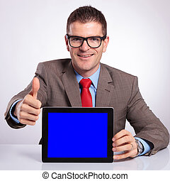 young business man presents tablet and shows thumb up