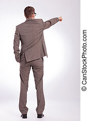 back of a young business man pointing with a hand in pocket