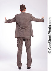 back of a young business man with both thumbs up - full...
