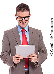 young business man holds tablet with both hands and reads