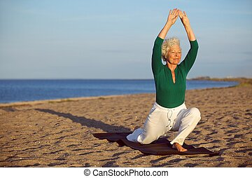 Senior woman stretching on the beach