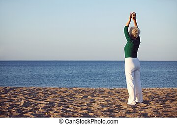 Senior woman doing yoga exercise - Senior woman raises her...