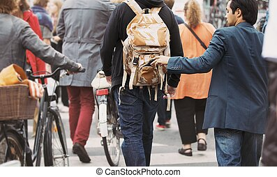 Thief pulls wallet out of a man backpack - Young man taking...