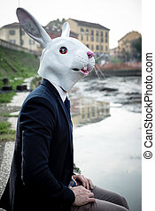rabbit mask man in a desolate landscape river
