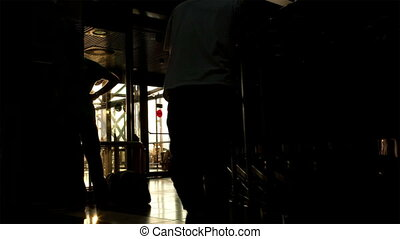 Man pulling airport luggage trolleys - Back-lit man pulling...