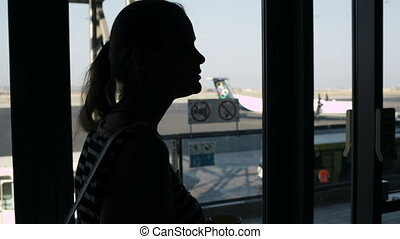 Young woman drinking coffee at the airport - Back-lit...