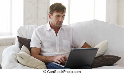 man working with laptop at home - technology and lifestyle...