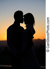 silhouette of bride and groom on Sunset background -...