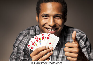 lucky guy - smiling dark-skinned young man holds the winning...