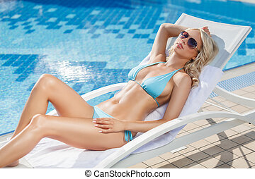 Relaxing on the deck chair Beautiful young women relaxing on...