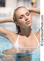 Hot summer day Attractive young women in bikini relaxing in...
