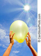 Child throws, catches the balloon against the blue sky with...